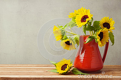 Autumn wallpaper. Sunflowers in red vase on wooden table