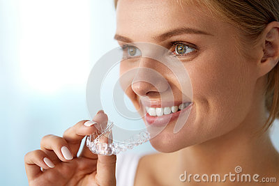 Smiling Woman With Beautiful Smile Using Invisible Teeth Trainer
