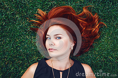 Close up portrait of young Caucasian beautiful girl woman with red brown hair lying on green grass in park. View from above