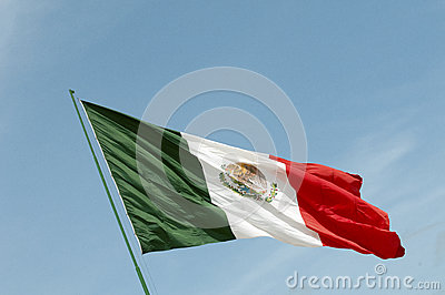 Mexican National Flag waving against a blue sky