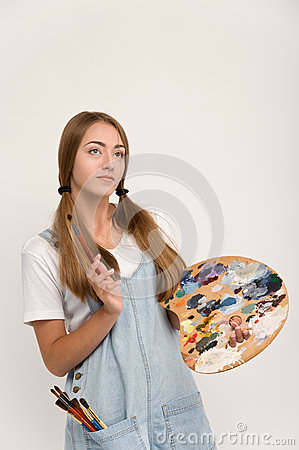 Young artist holding a brush to paint and palette.