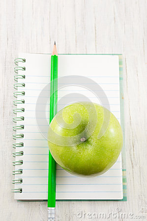 Apple on top of a notebook.