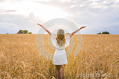 Happy woman in golden wheat