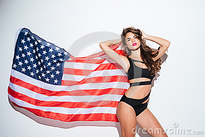 Beautiful young sexy girl posing in bikini with american flag