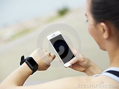 Woman with cellphone and fitness tracker