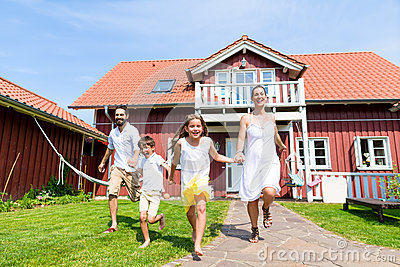 Happy family running on meadow in front of house