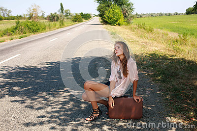 Tired woman in with suitcase hitchhiking on road in country
