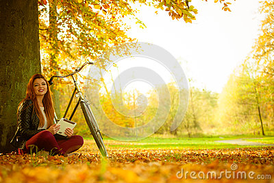 Girl under tree with bike.