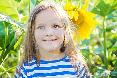 Girl with funny face among sunflower filed
