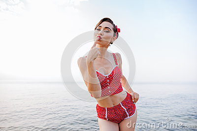 Happy pretty pinup girl in red swimsuit sending a kiss