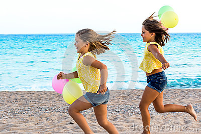 Two little sisters running together on beach.
