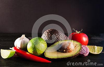 Ingredients for guacamole, avocado, lime, onion, garlic, tomato,