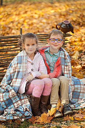Two friends: a boy and a girl in autumn park sitting on wooden bench near a fence