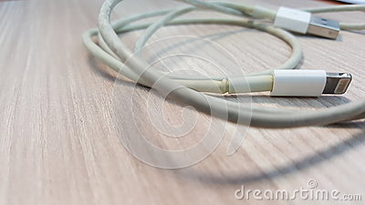 Old smart phone charger wire on laminate floor.