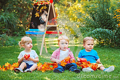 Group of three white Caucasian toddler children kids boys and girl sitting outside in summer autumn park by drawing easel