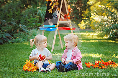 Group of two white Caucasian toddler children kids boy and girl sitting outside in summer autumn park by drawing easel