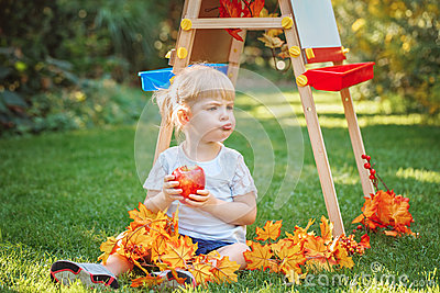 White Caucasian toddler child kid girl sitting outside in summer autumn park by drawing easel eating apple looking away