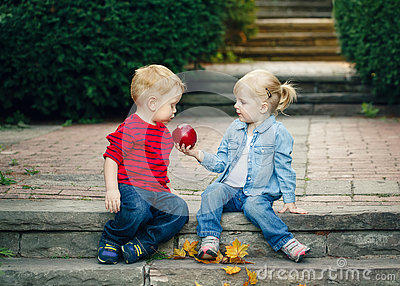 Group portrait of two white Caucasian cute adorable funny children toddlers sitting together sharing apple food