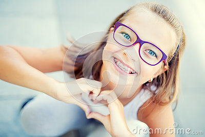 Smiling little girl in with braces and glasses showing heart with hands