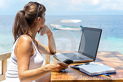 Young pretty woman freelancer writer working with laptop notepad and phone infront of blue tropical sea