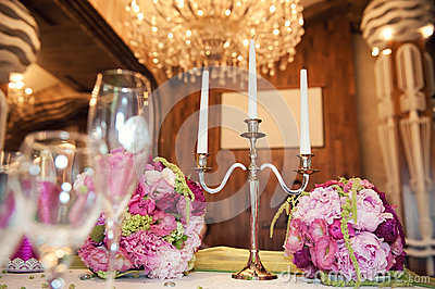 Gorgeous flower arrangement at the wedding table. And candleholder for three candles on the background of chandeliers