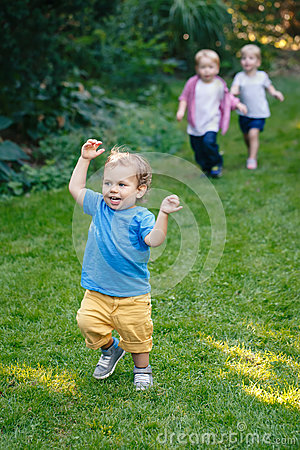 Group portrait of three white Caucasian blond adorable cute kids playing running in park garden outside