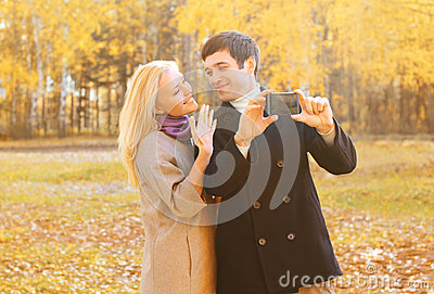 Happy pretty smiling young couple taking picture self portrait on smarphone outdoors in sunny autumn