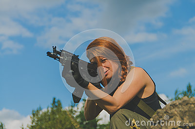 Redhead girl military aim from the weapon
