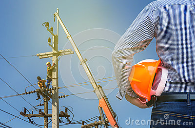 Electrical engineer holding safety helmet with electricians working on electric power pole with crane