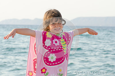 Beautiful little girl smiling at seaside in pink butterfly towel