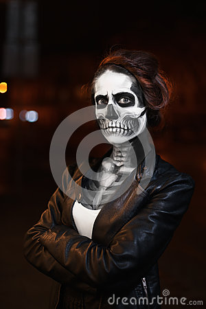 Young woman walking on avenue. Face art for Halloween party. Street portrait. Waist up. Night city background