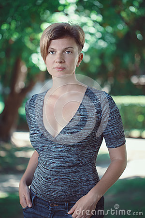 Portrait of young middle aged white caucasian girl woman with short hair stylish haircut  in tshirt looking in camera