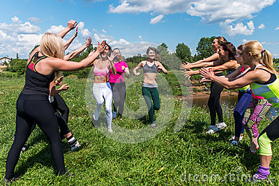Group of excited women crossing the finshline a marathon running on grassy land in park.