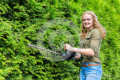 Young dutch woman holding hedge trimmer at conifers