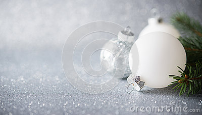 Silver and white xmas ornaments on glitter holiday background. Merry christmas card.