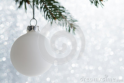 White decorative ball on the xmas tree on glitter bokeh background. Merry christmas card.