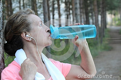 Mature woman drinking water after exercising - outdoors