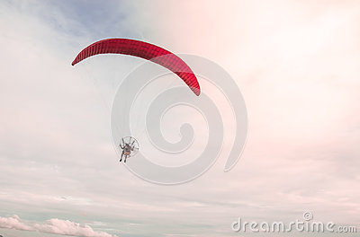 A man soaring into the sky with paramotor extreme sport adventure in summer day time with a clear sky background.