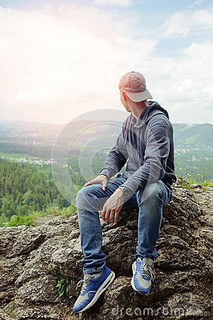 Male resting and enjoying the mountain sitting on rock
