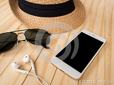 Travel accessories concept. Smartphone, earbuds, sunglasses, hat