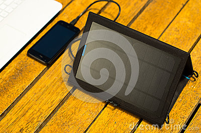 Portable solar charger sitting on wooden surface next to laptop computer and mobile phone, as seen from above, modern