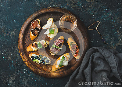 Italian crostini and glass of wine on round serving tray