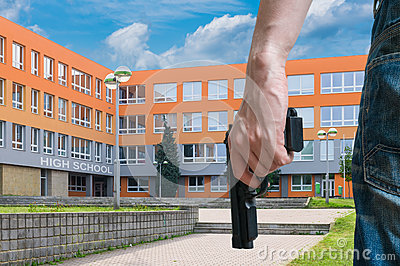 Gun control concept. Young armed man holds pistol in hand in public near school.