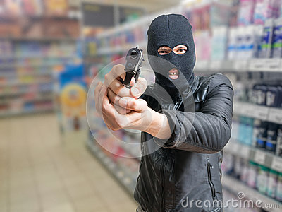 Robbery in store. Robber is aiming and threatening with gun in shop