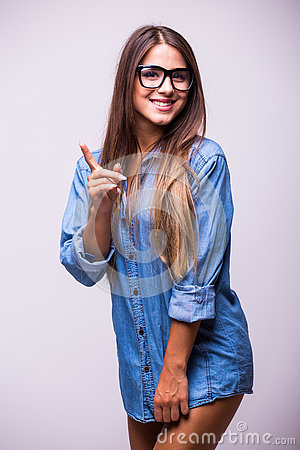 Girl in jeans shirt with glasses posing with different gesture in studio