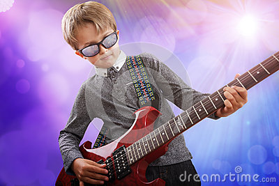 Boy playing electric guitar in talent show on stage