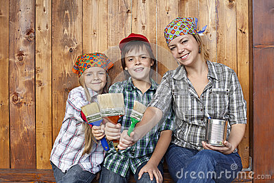 Woman with kids ready to paint the shed