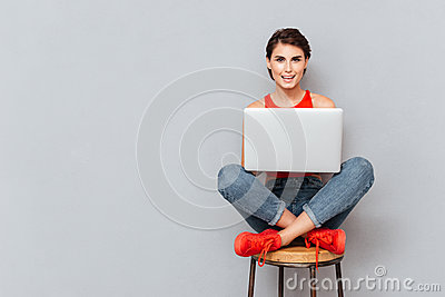 Young beautiful smiling girl using laptop pc computer for study