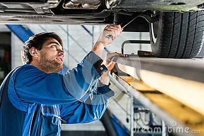 Mechanic Changing Tire From Suspended Car At Automobile Shop