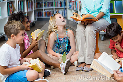 Low section of teacher with children reading books